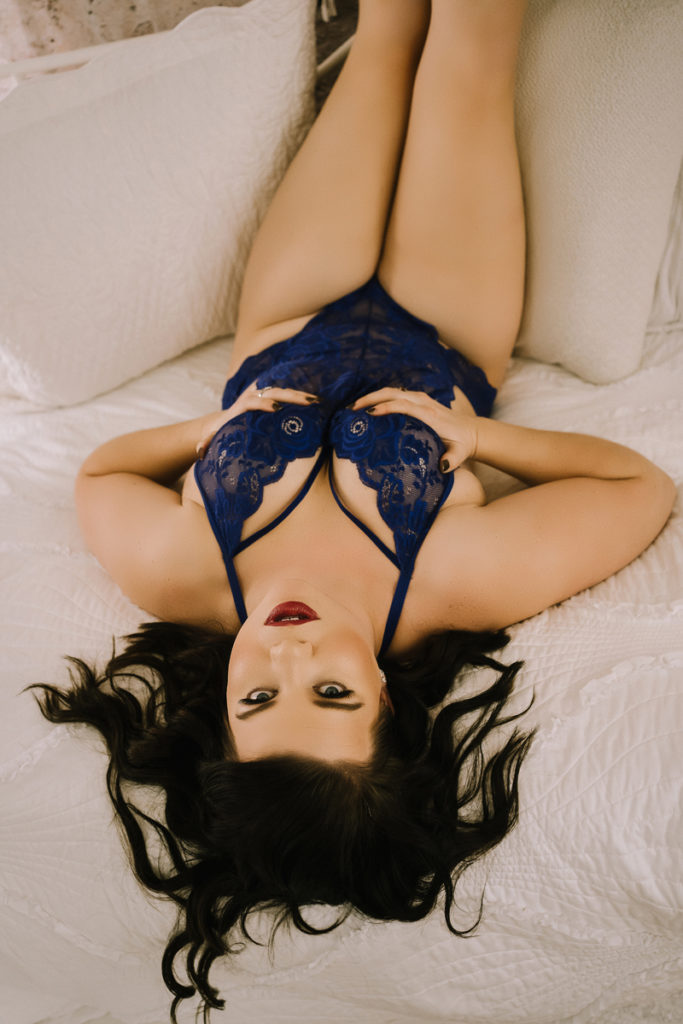 Empowerment Boudoir Photography, woman in blue lingerie lays in bed